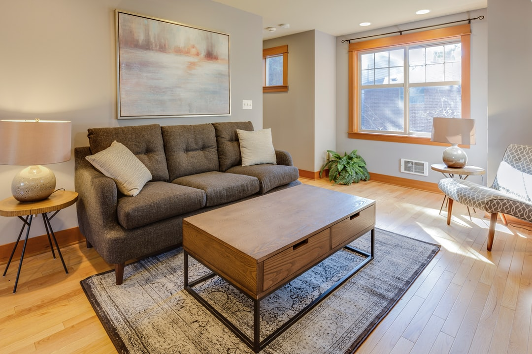 brown couch with two white throw pillows