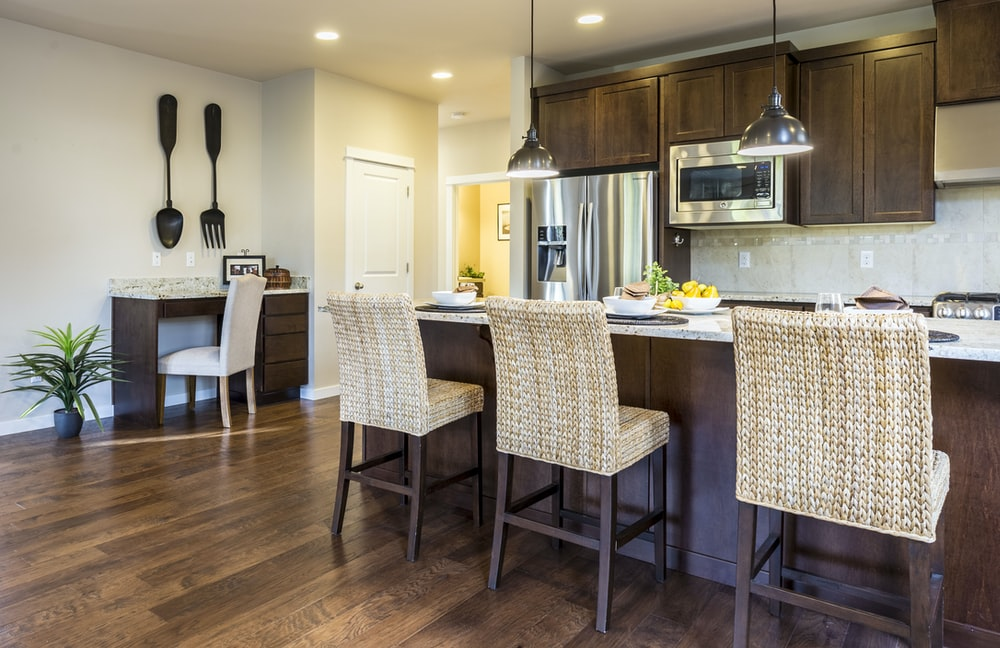 three brown wooden chairs in front of kitchen counter