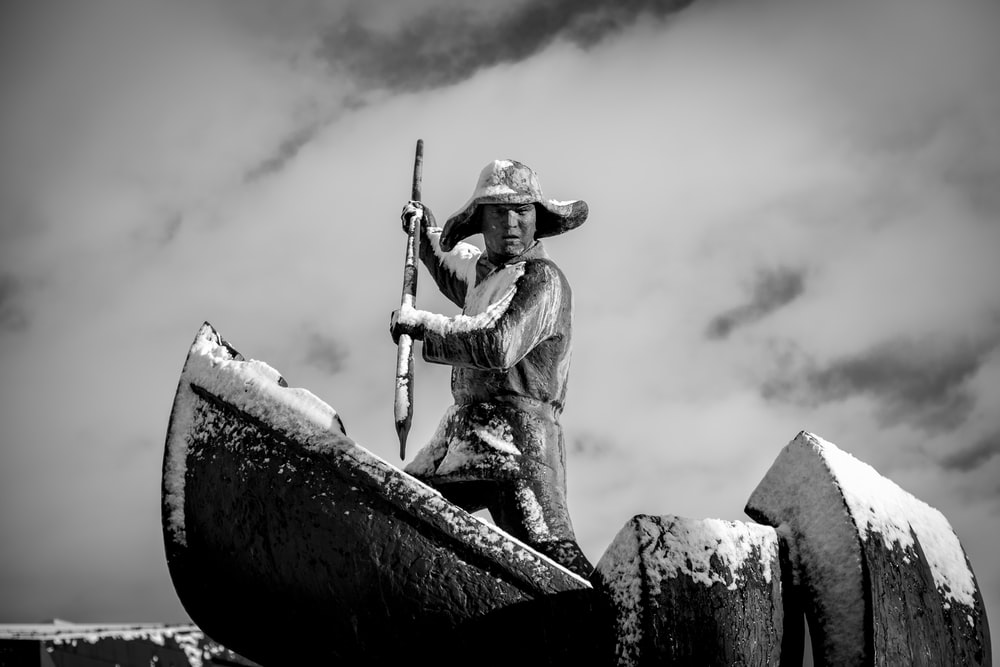 grayscale photography of man standing on boat