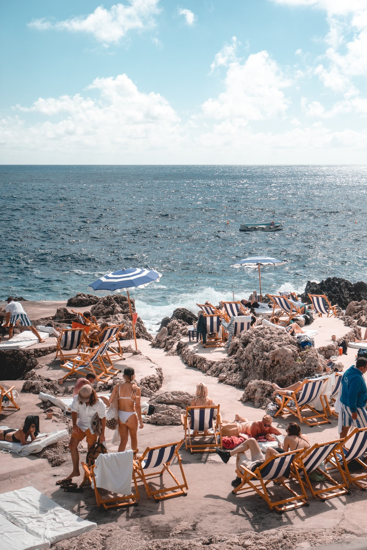people standing near beach line