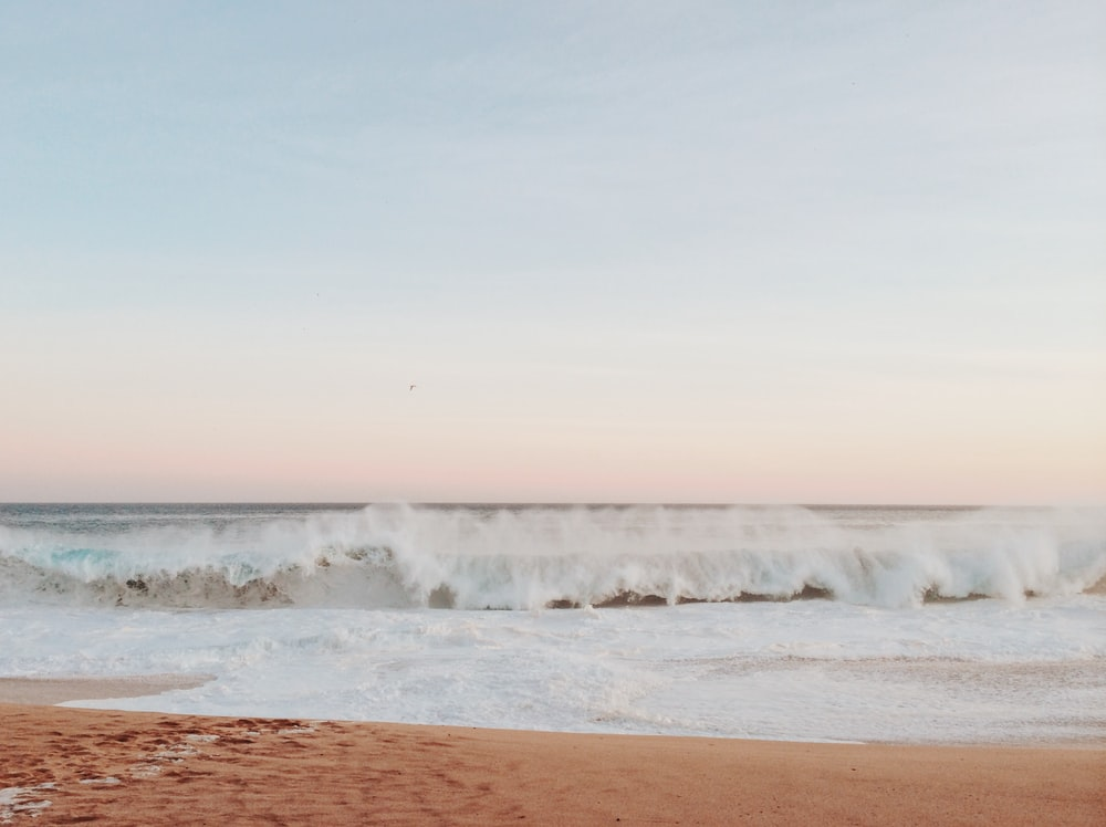 time lapse photography of waves on seashore during daytime