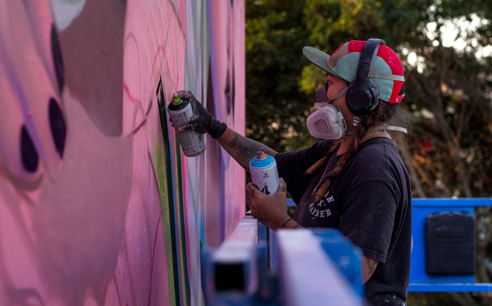 person spray painting wall