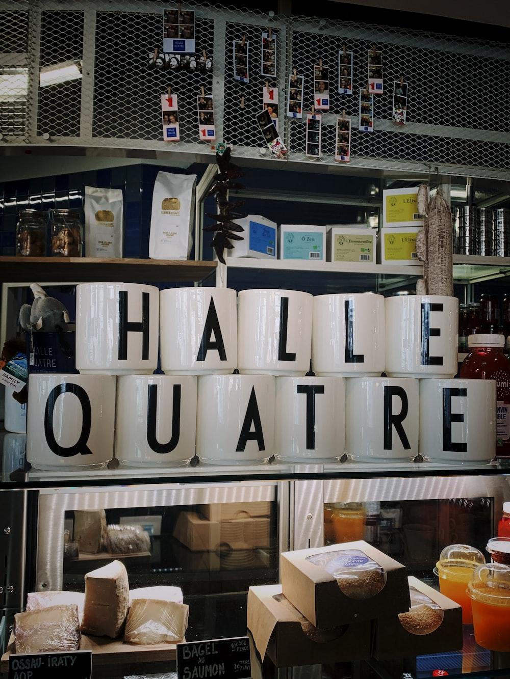 white ceramic mugs with Halle Quatre letters