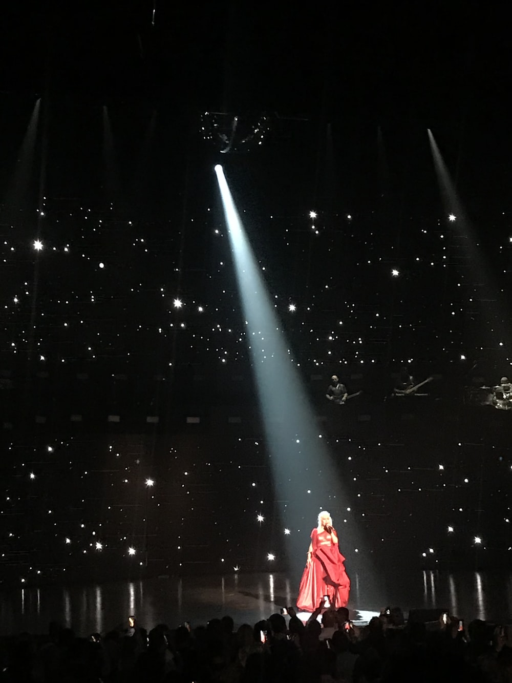 woman wearing red dress performing stage