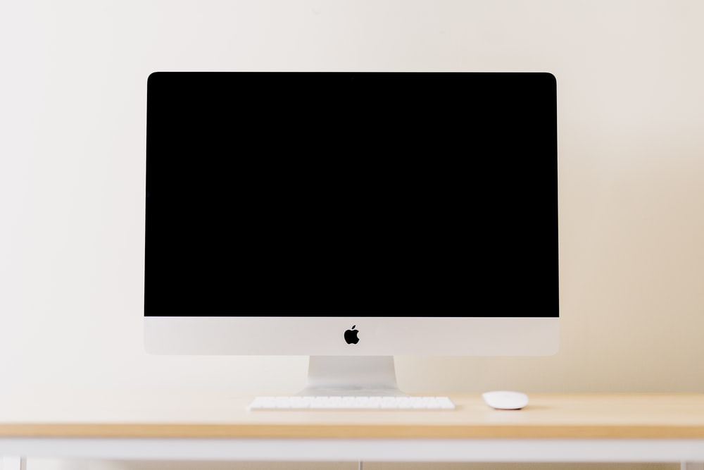 silver iMac besides white Apple Magic keyboard and mouse
