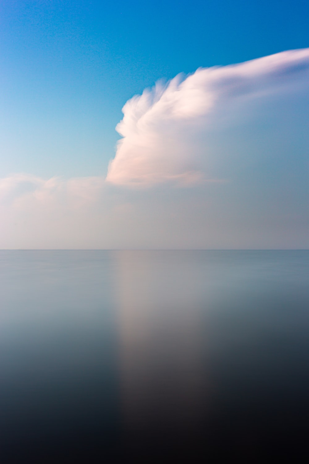 calm sea under clear blue sky and white clouds