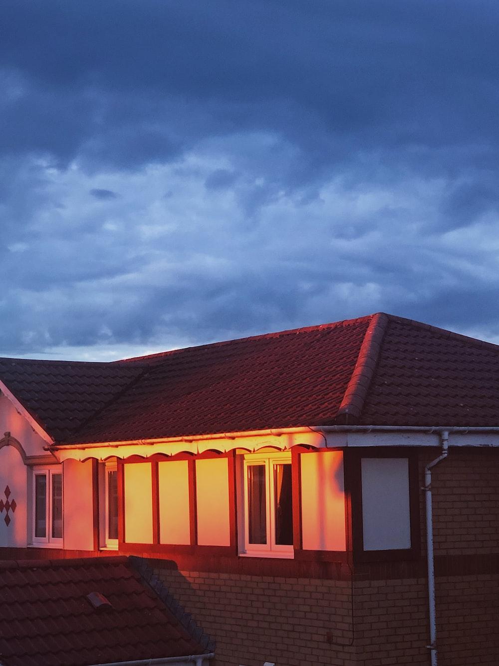 maroon house under cloudy sky