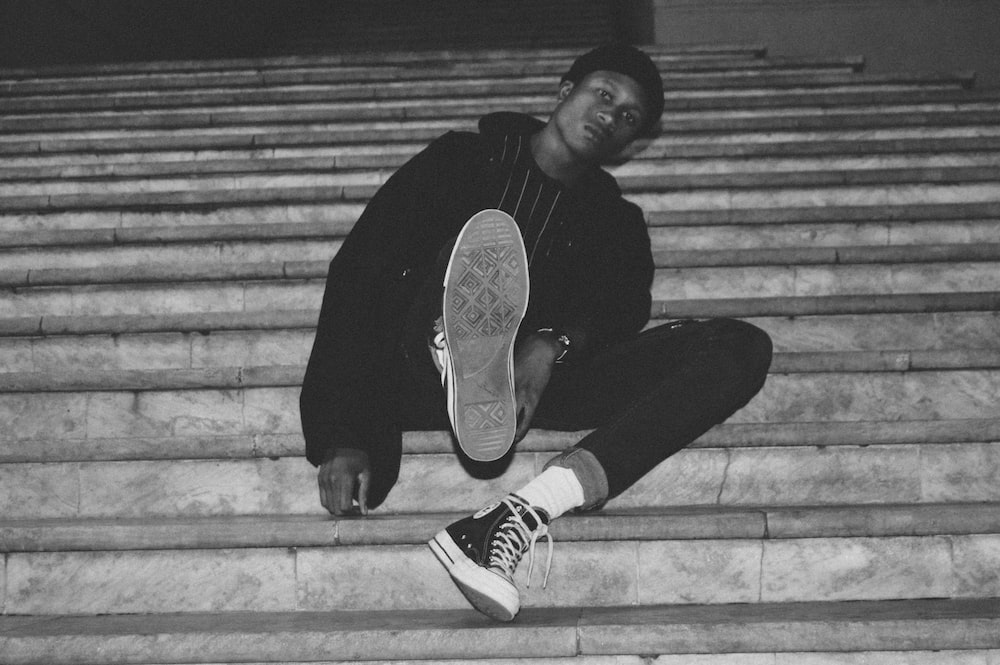 grayscale photography of man sitting on stairs