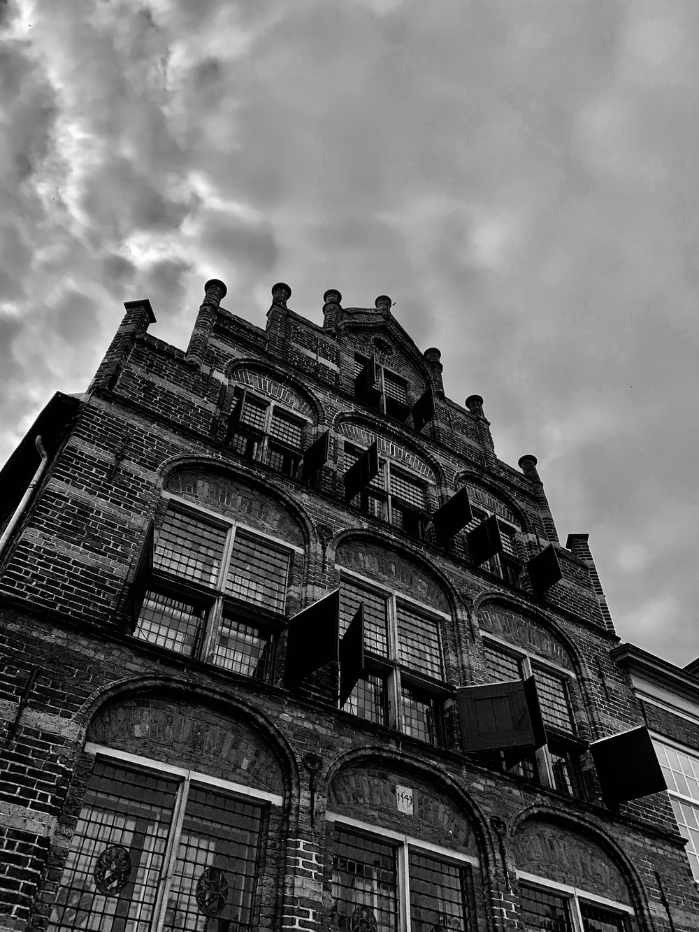 grey cloud hovering above antique brick building