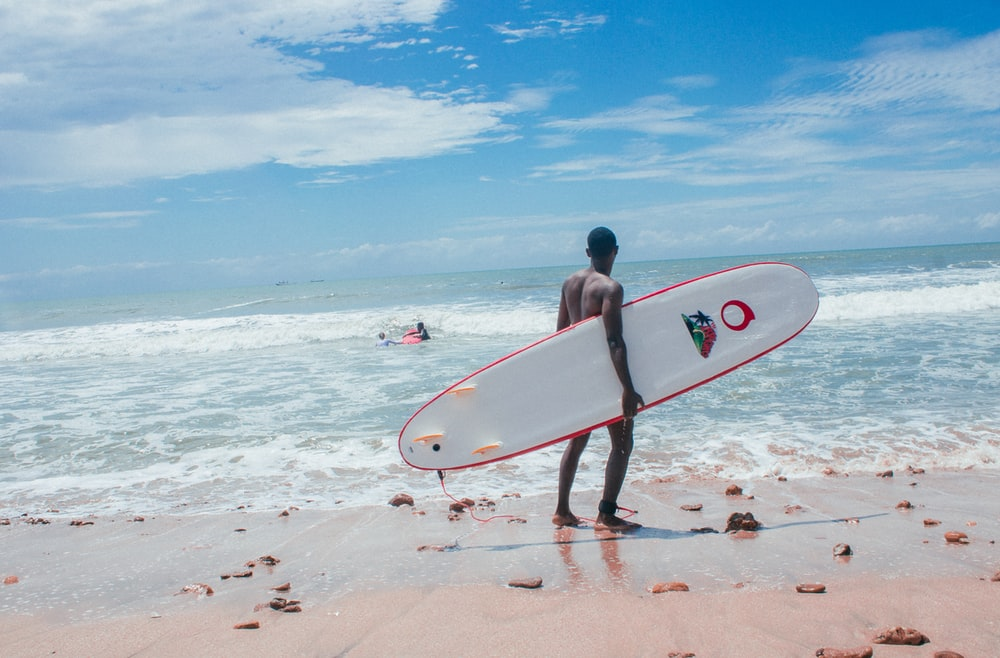 man with white and red surfboard standing in beach