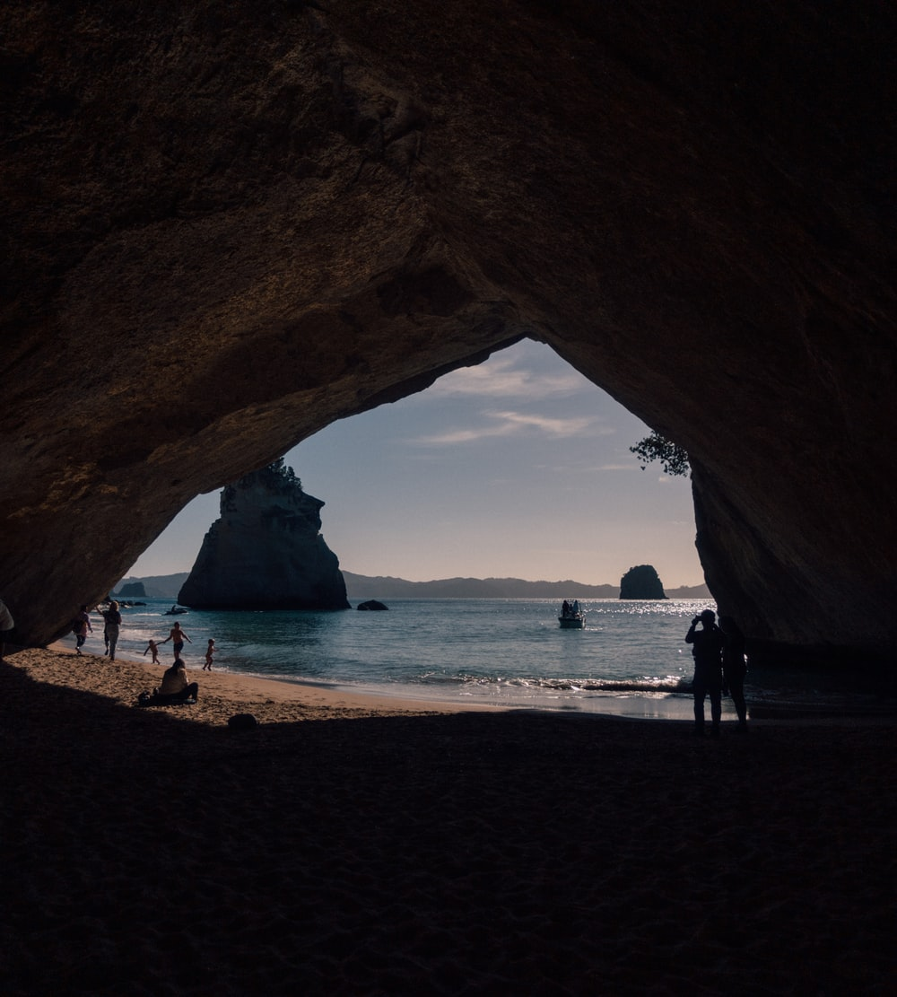 cave leading to a white sand beach