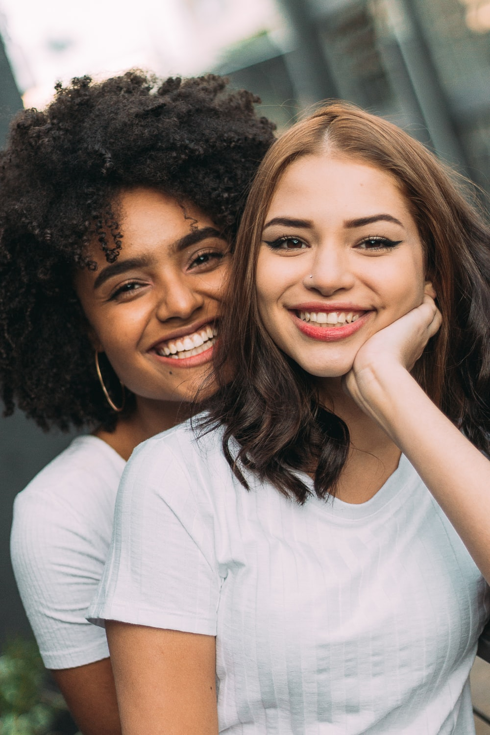 two smiling woman standing near white wall