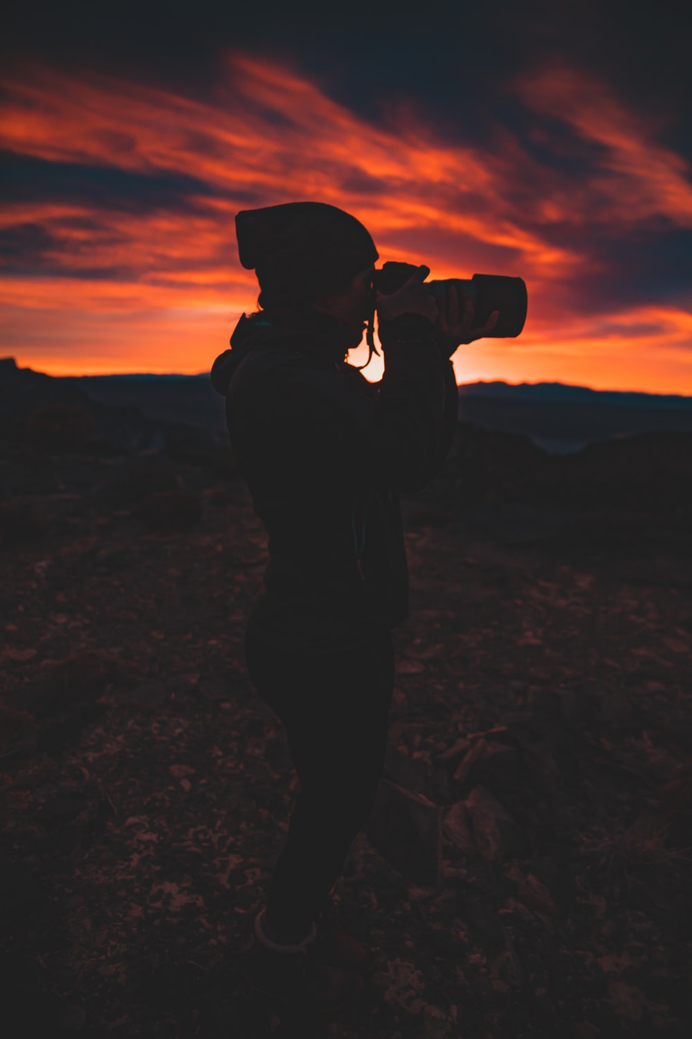 silhouette of person holding camera during golden hour