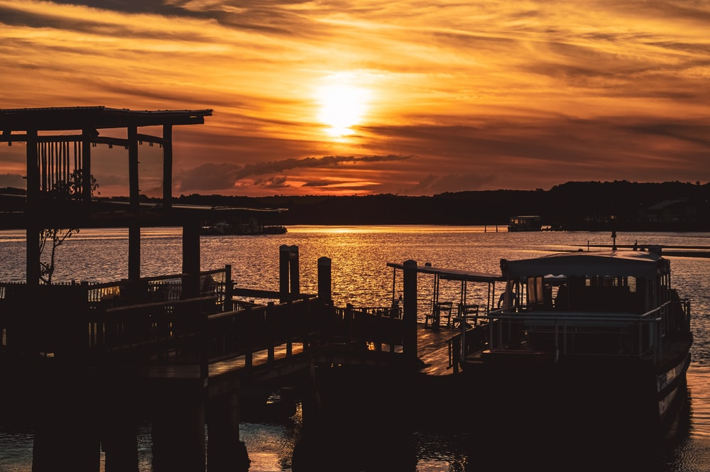 silhouette of dock and boats during sunset