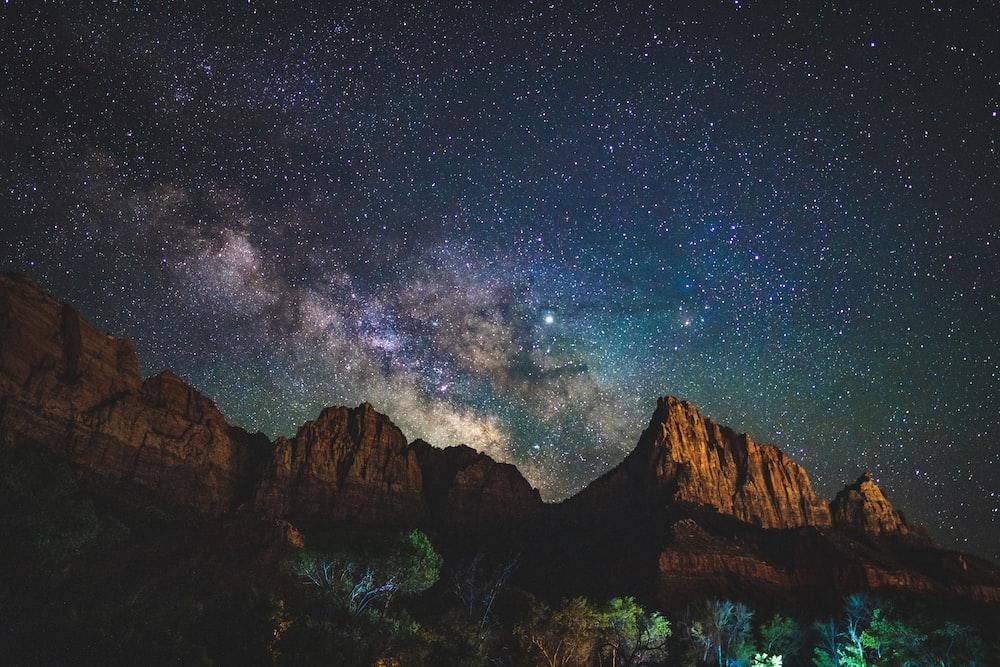 rock mountain under starry night sky