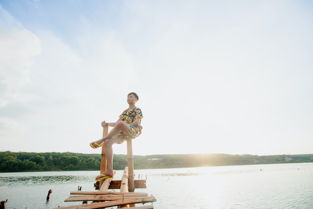 man sitting on brown bamboo sea dock