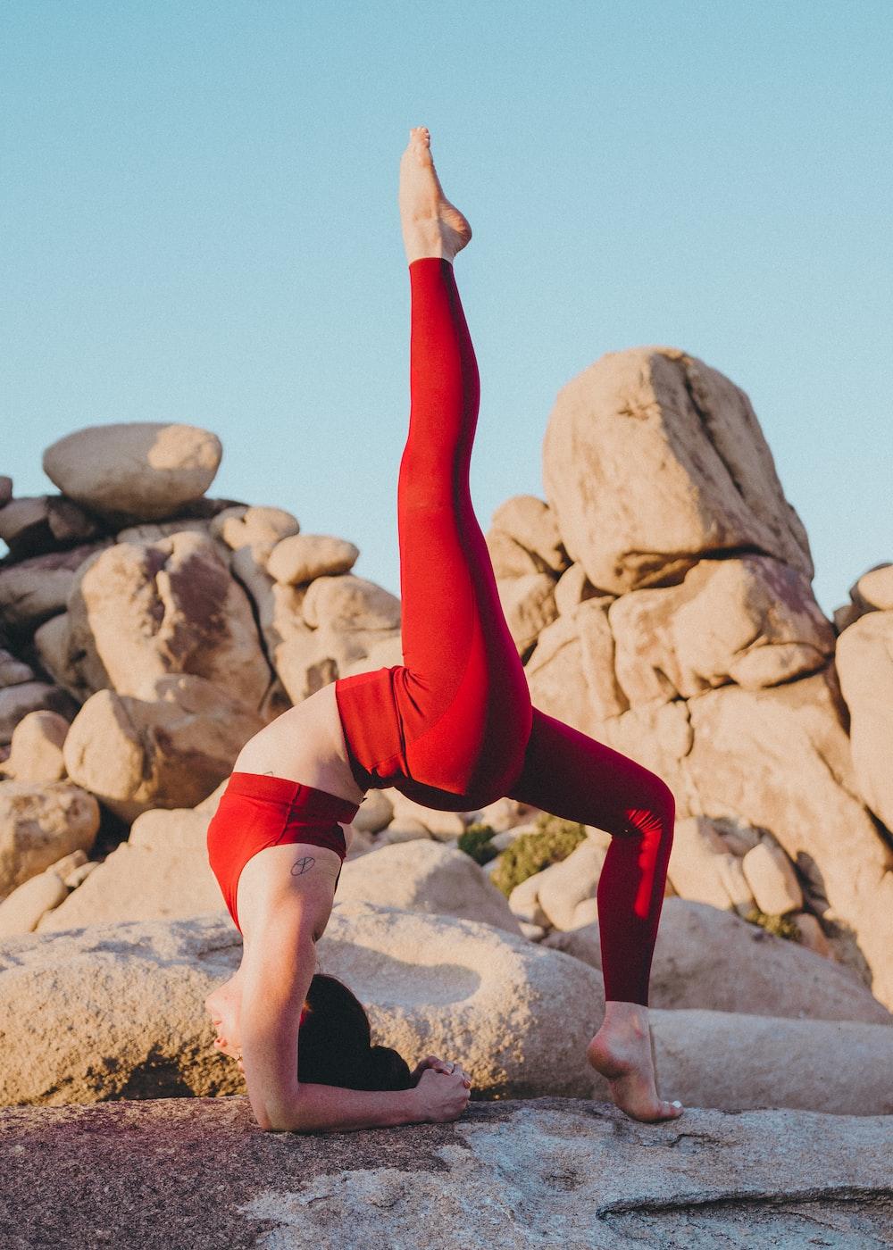 woman doing yoga near rock during daytime