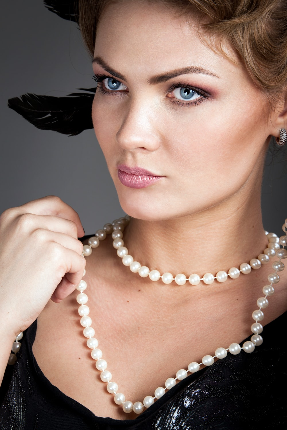 woman holding her white beaded necklace