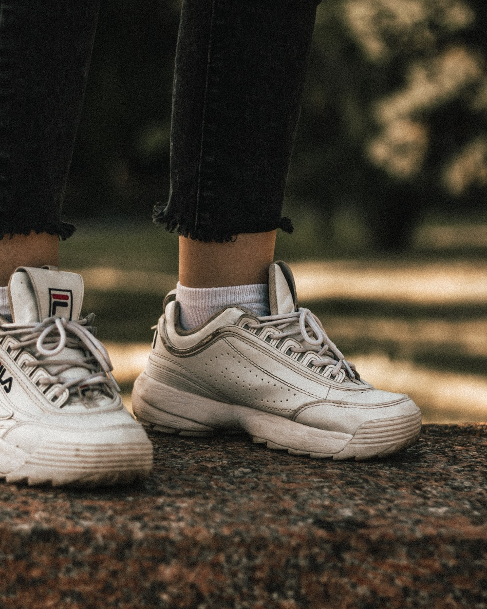 person wearing white Fila low-top sneakers