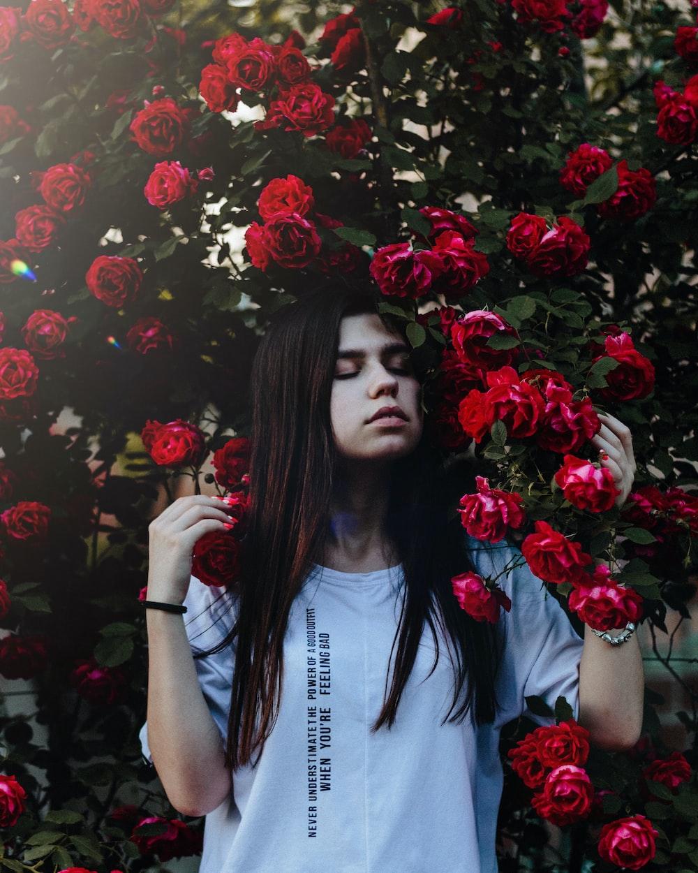 woman wearing grey shirt beside red rose flowers