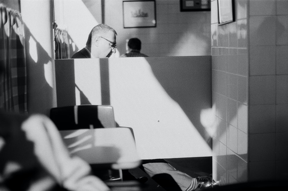 greyscale photo of man sitting inside room