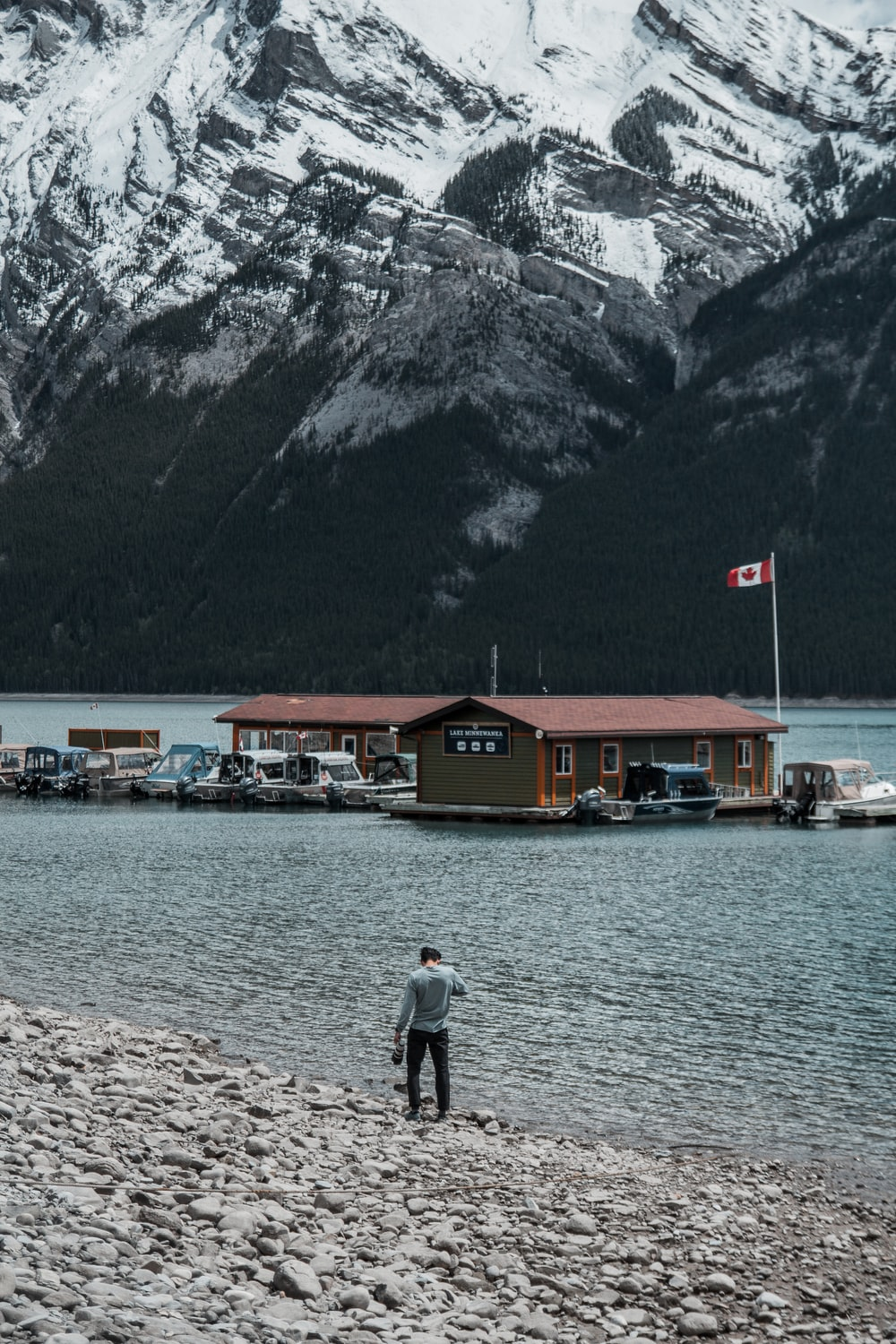 person walking near seashore viewing houses and mountain