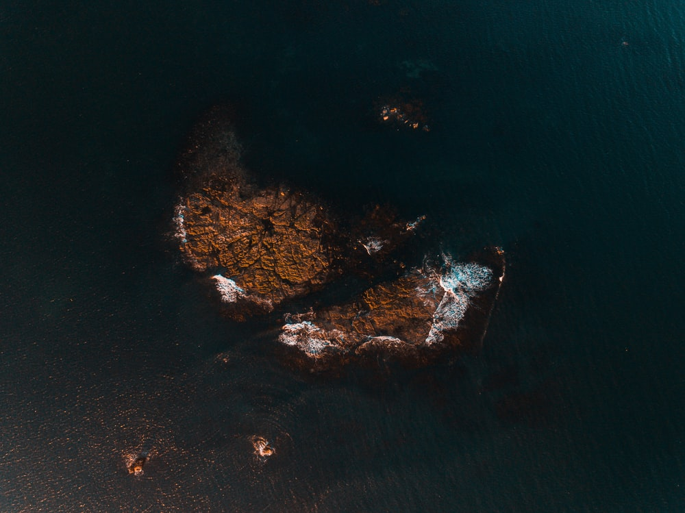 aerial photography of brown rock formation near body of water
