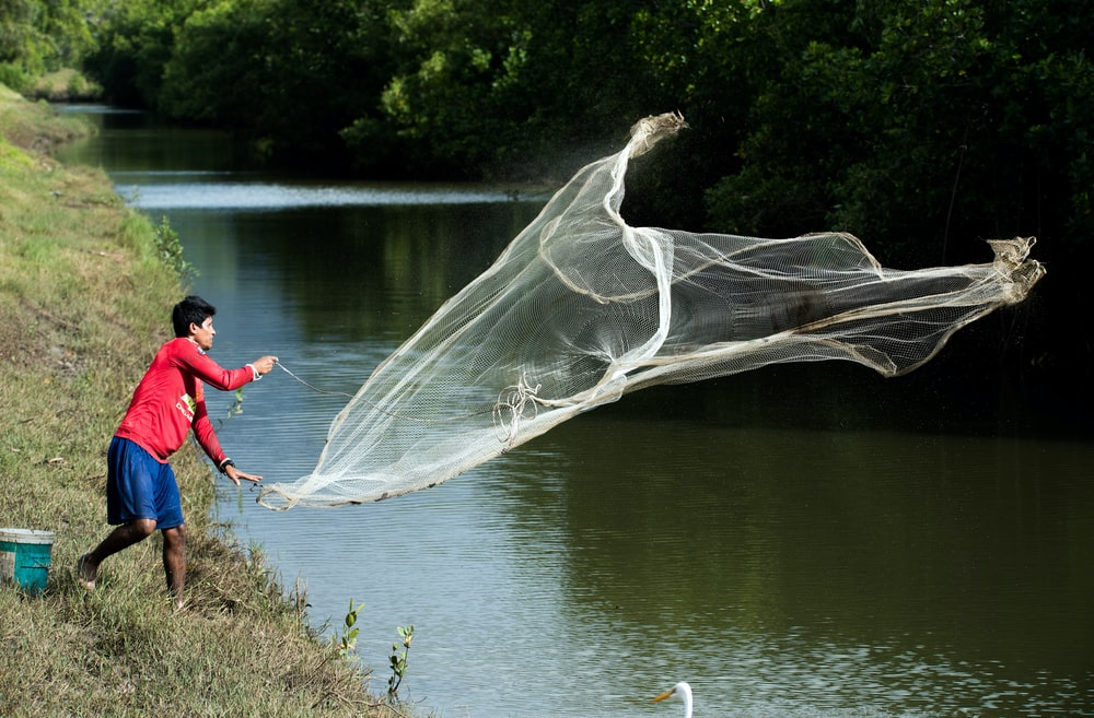 man throwing white fish net