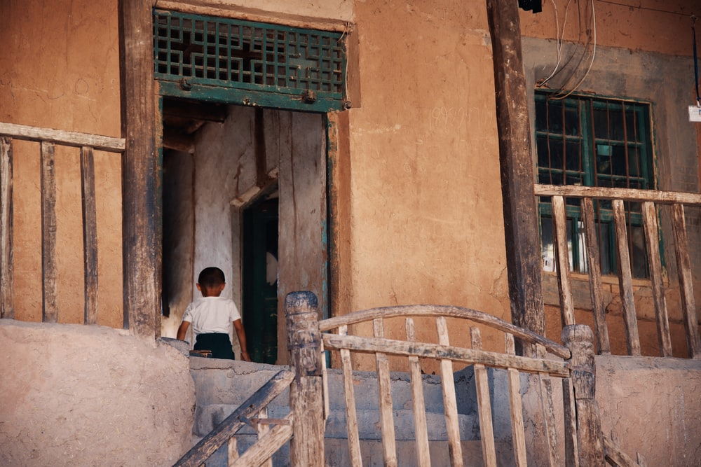 boy in white shirt and black bottoms standing inside house