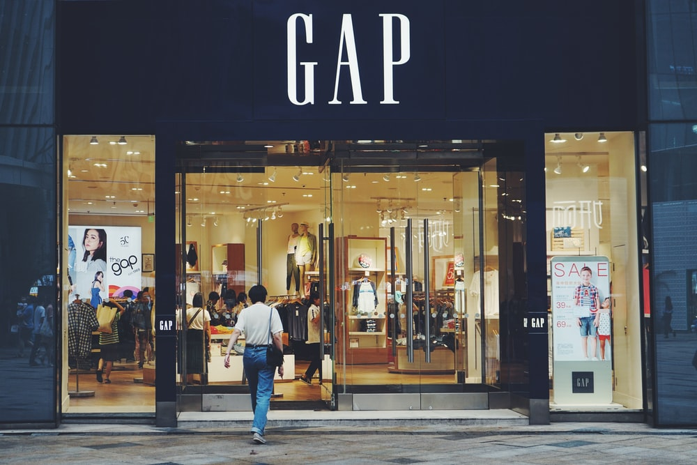 person in white shirt and blue jeans walking inside GAP store