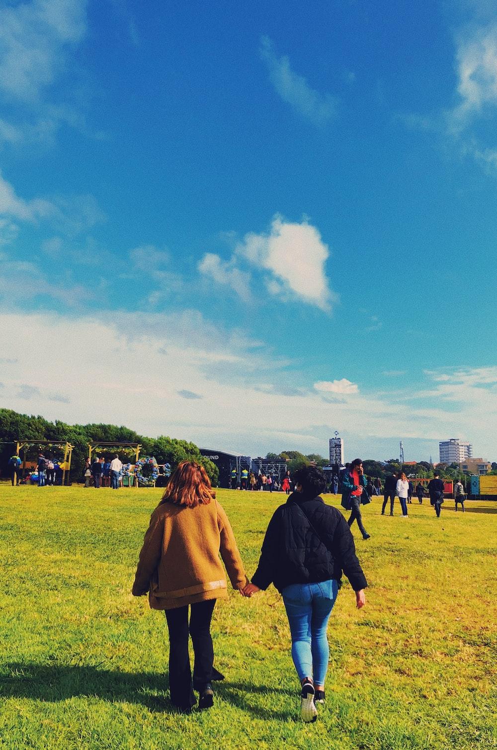 two women walking on grass field