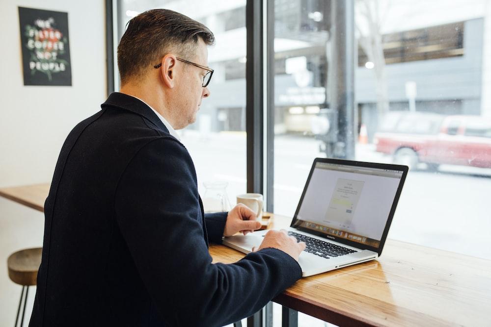 man wearing blue suit in front of MacBook Pro