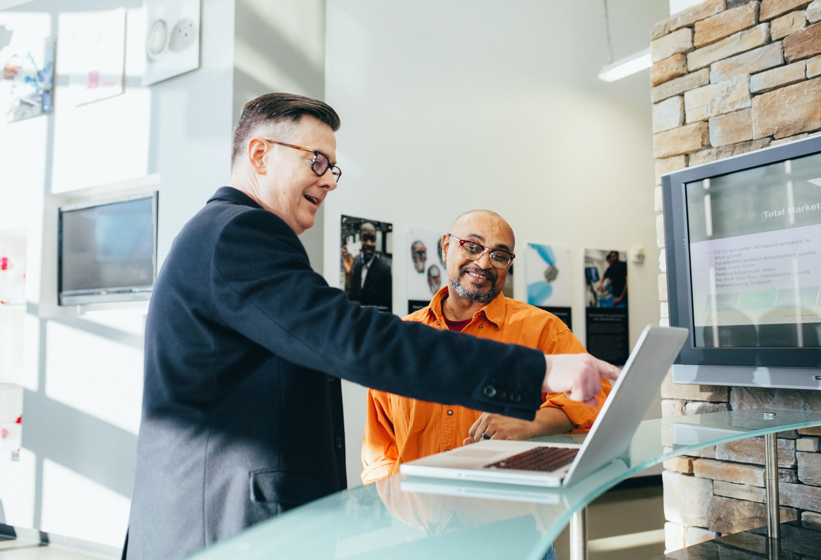 Male advisor with glasses showing another employee how something works on computer