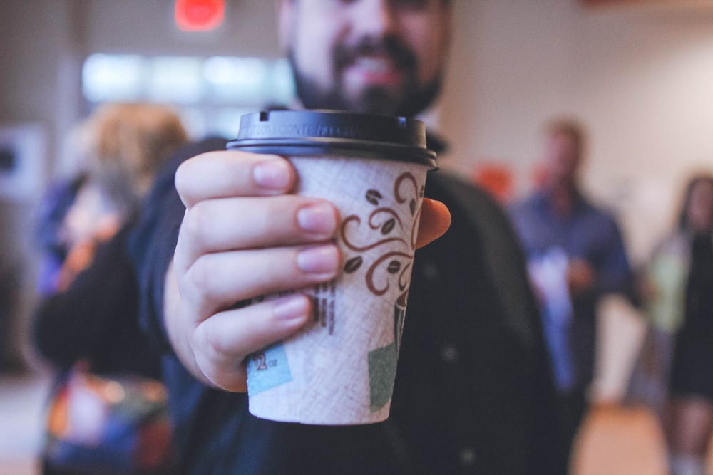 man holding white and black disposable cup