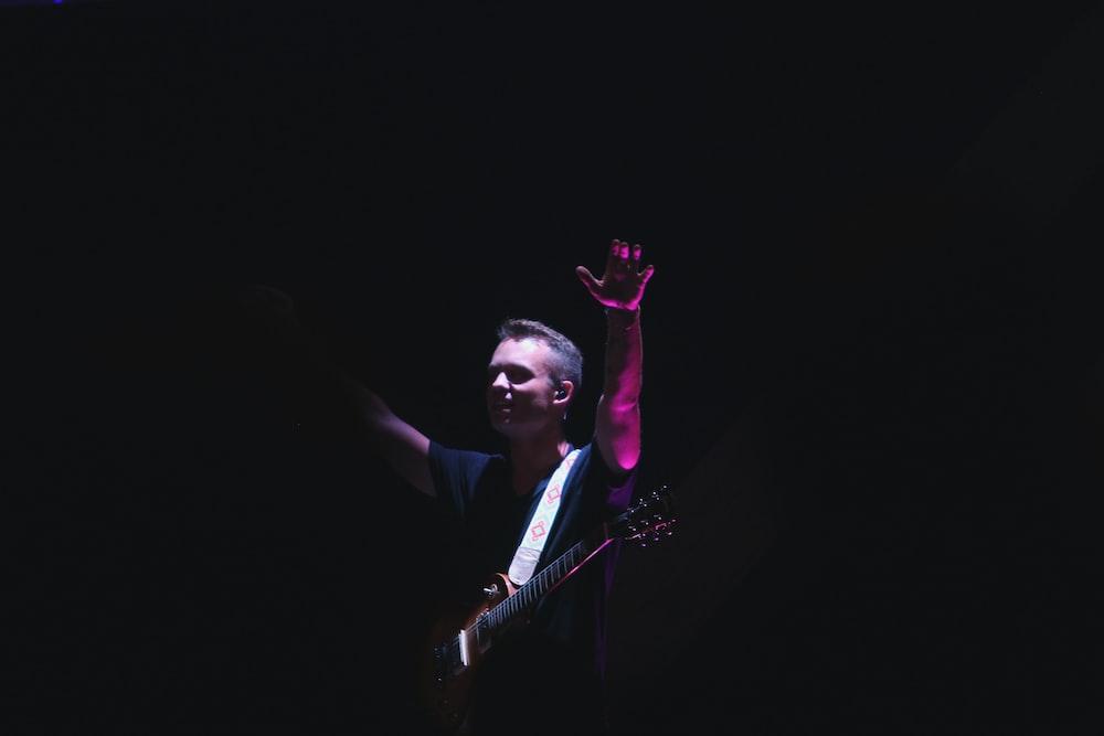 man in black crew-neck t-shirt holding guitar