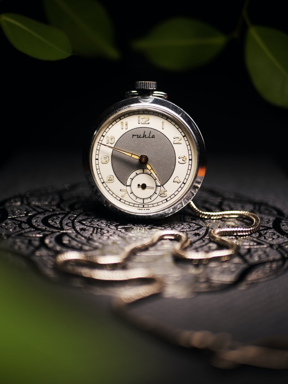 round grey pocket watch on grey surface