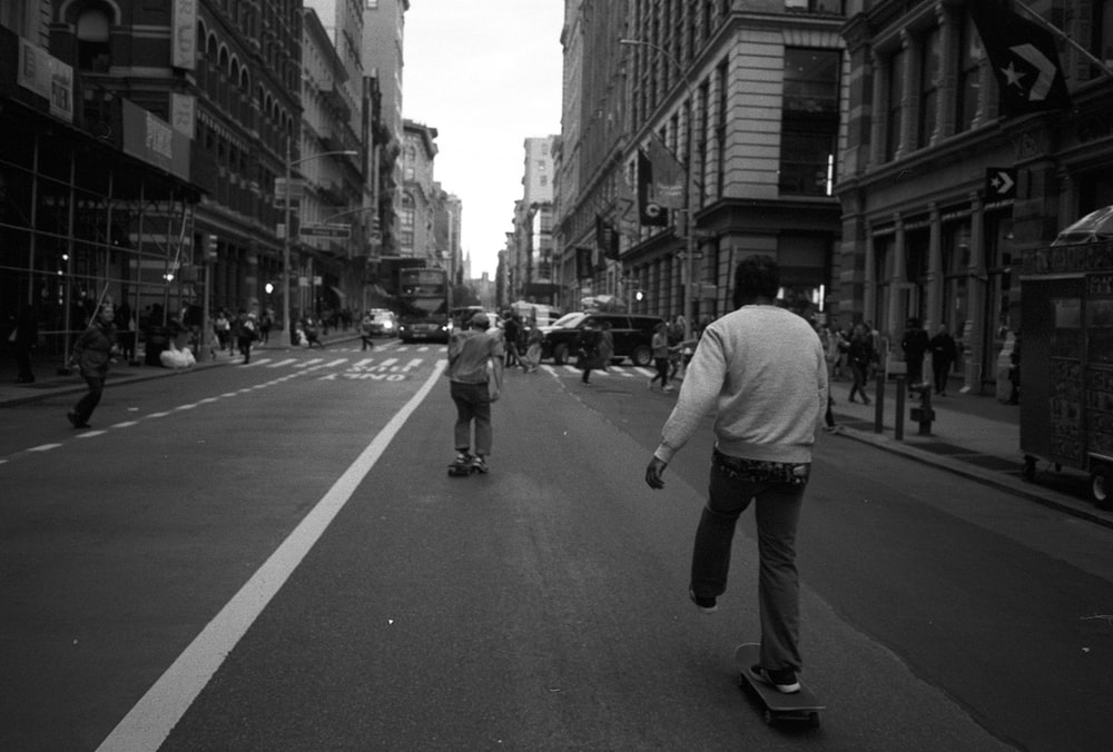 grayscale photo of skaters on the road