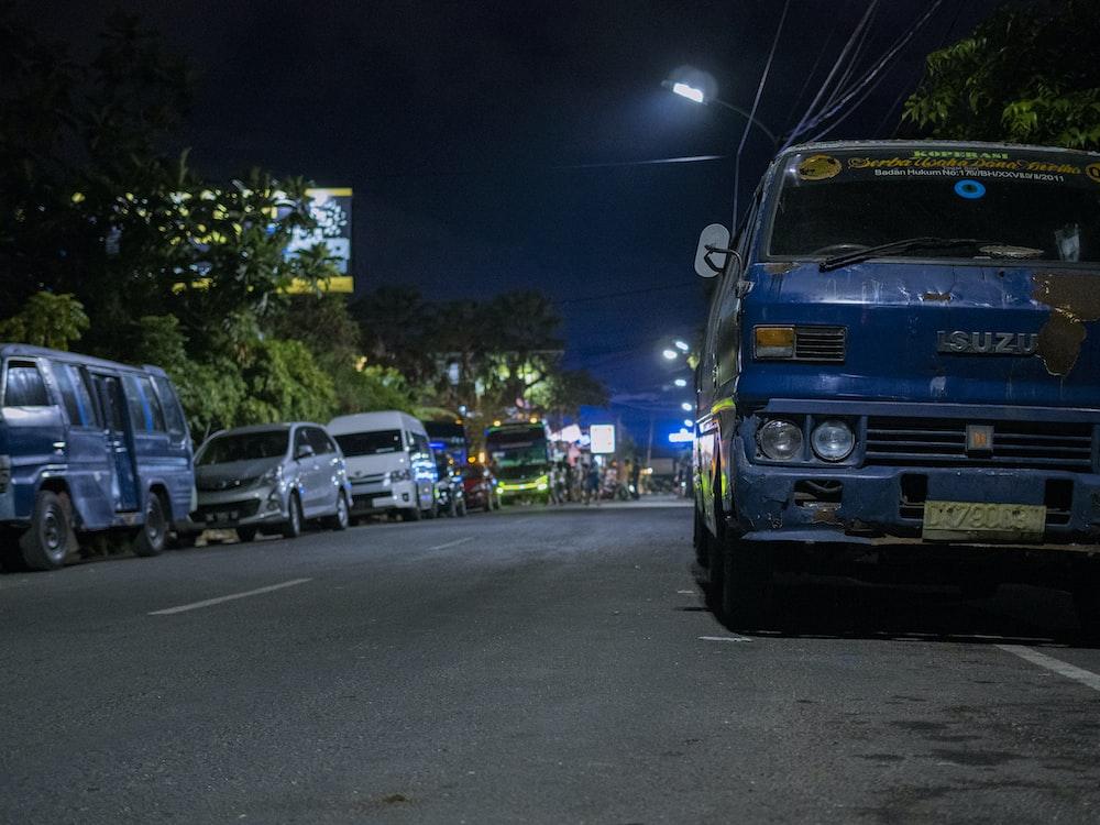 blue Isuzu truck on asphalt road