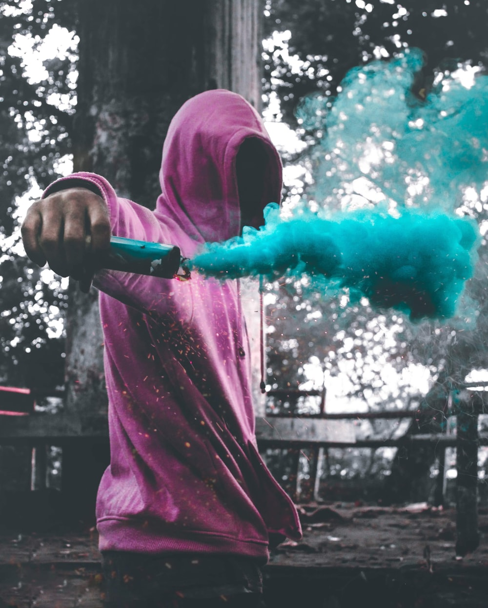 man wearing purple pullover holding smoke screen