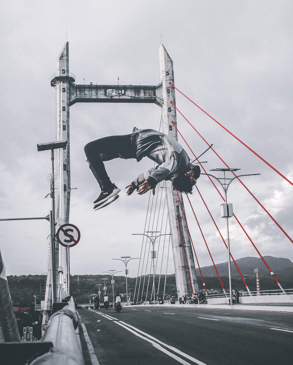 man in jacket and pants on concrete bridge