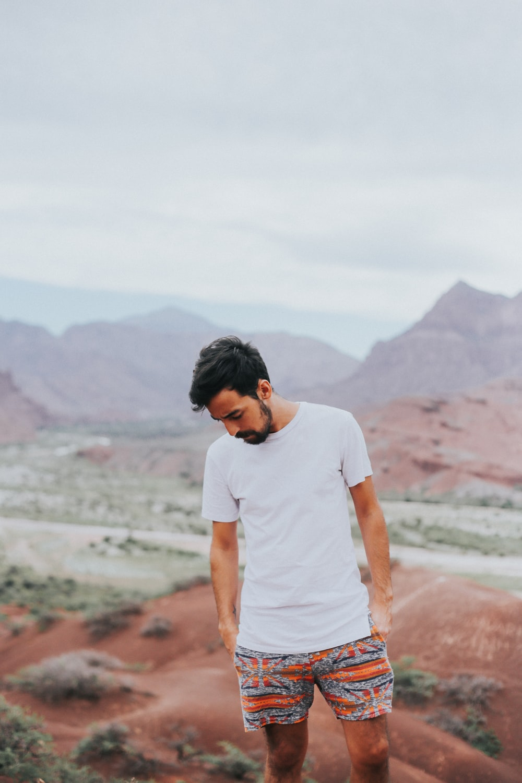 man wearing white crew-neck shirt across mountain