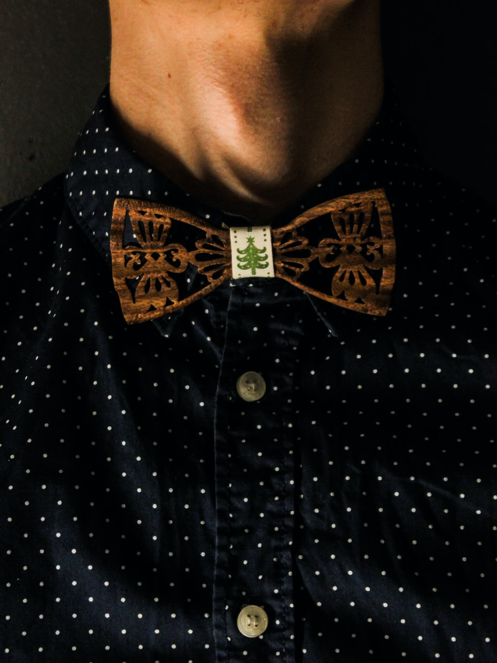 man in black and white polka dot shirt with brown bow tie