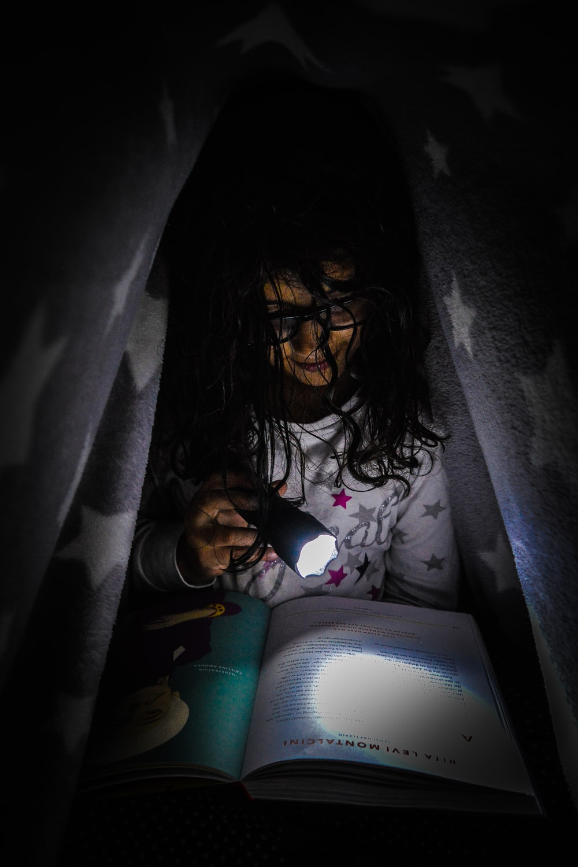 girl under the blanket reading by flashlight