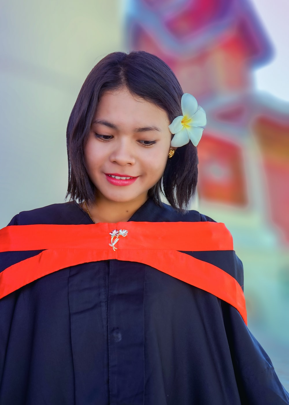 unknown person wearing academic dress taking selfie outdoors