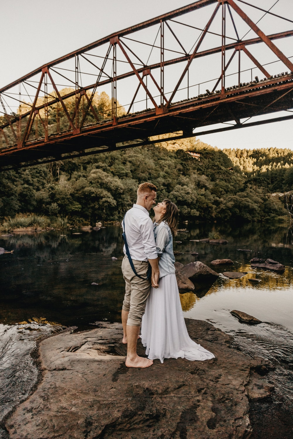 man and woman kissing under the bridge