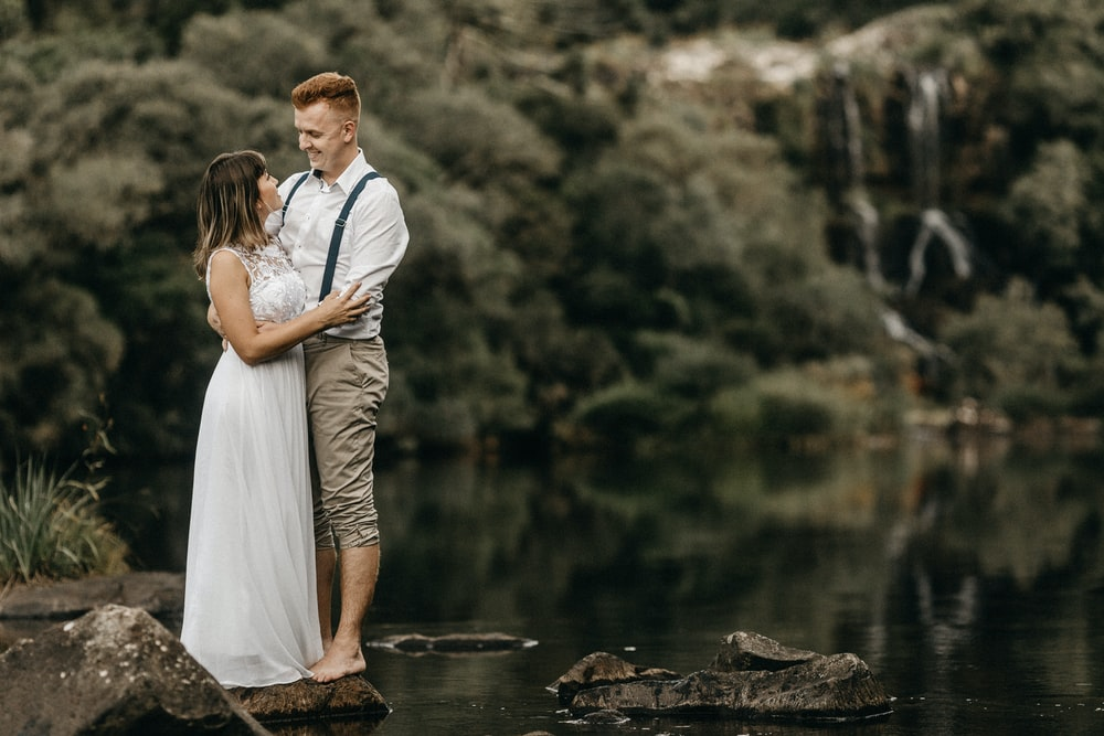 man and woman standing on rocks across green forest