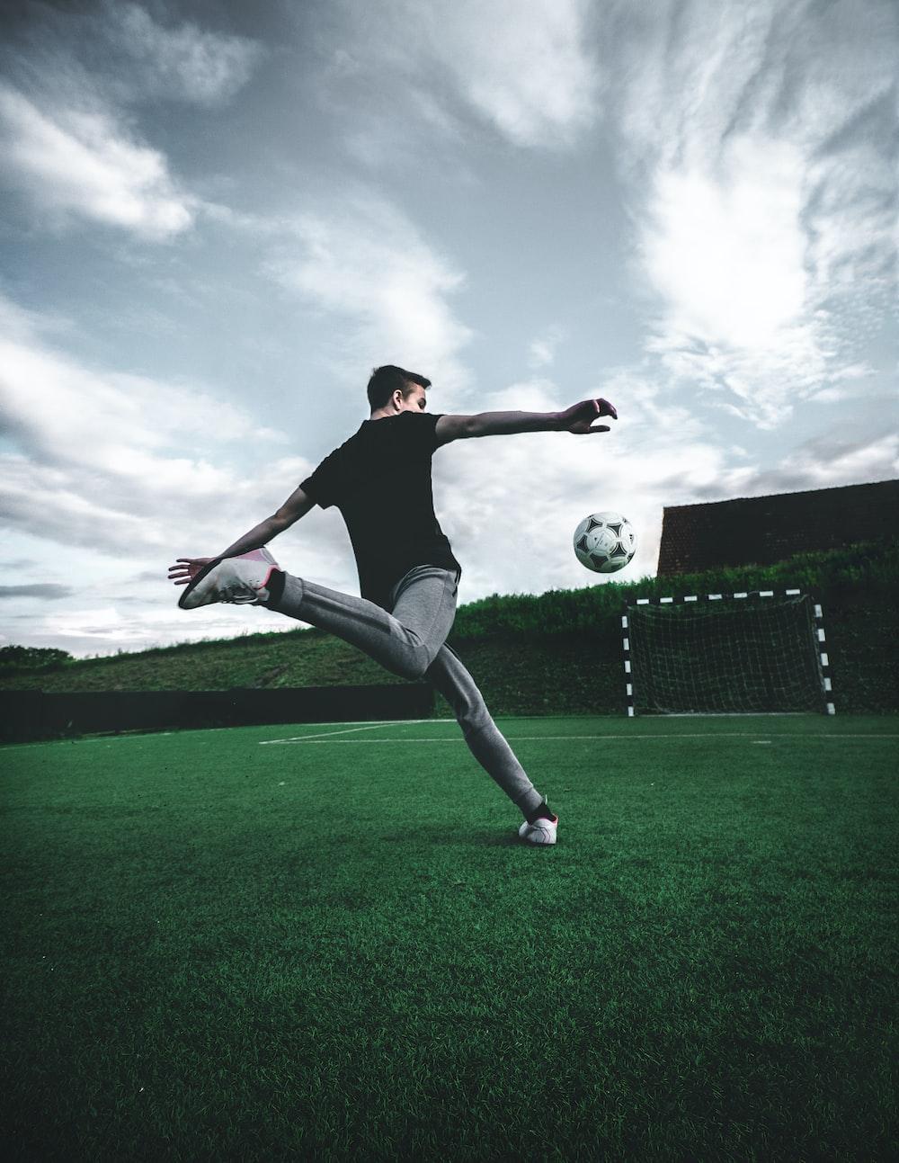 man playing soccer during daytime
