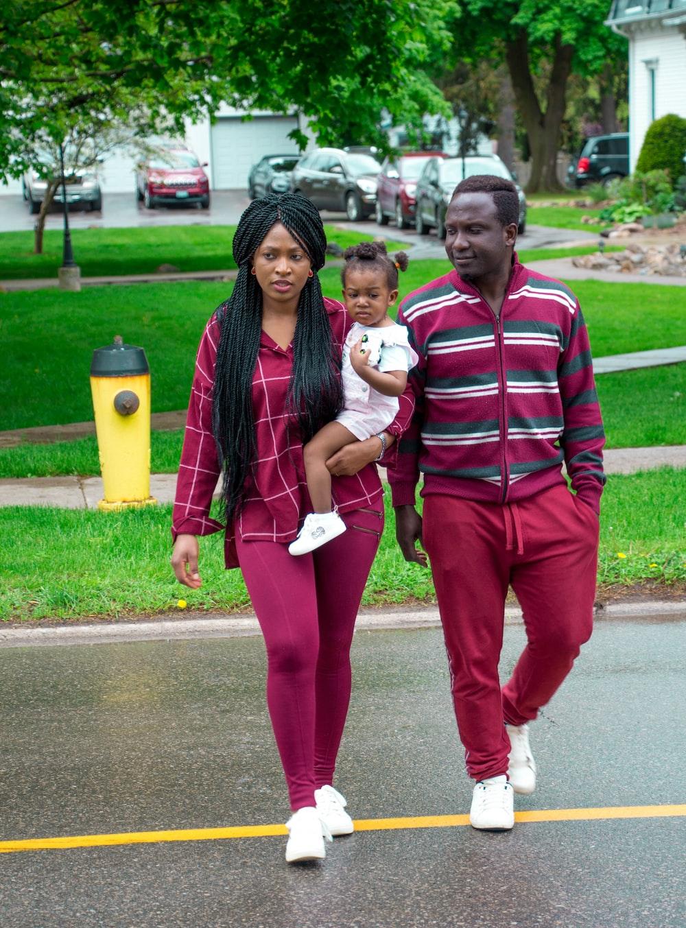 woman wearing purple long-sleeved shirt and purple leggings carrying toddler walking on streeet