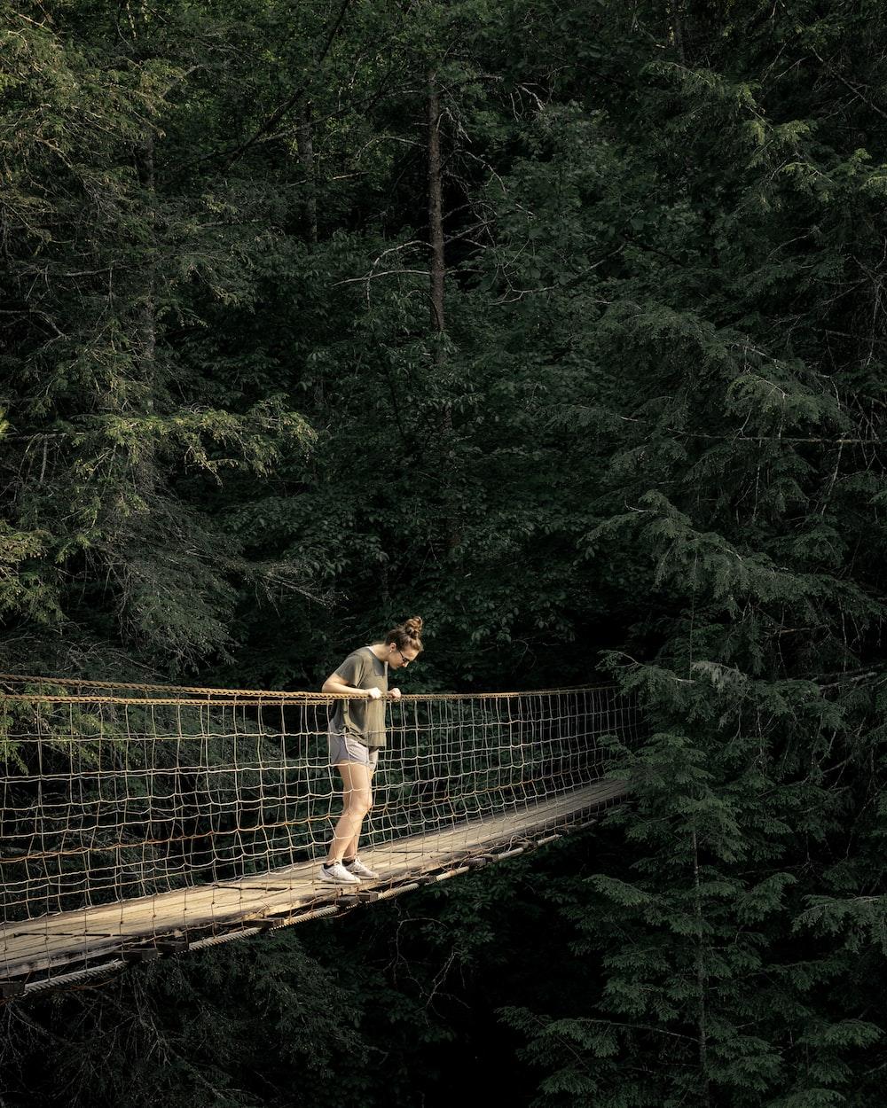 woman viewing downward on hanging bridge