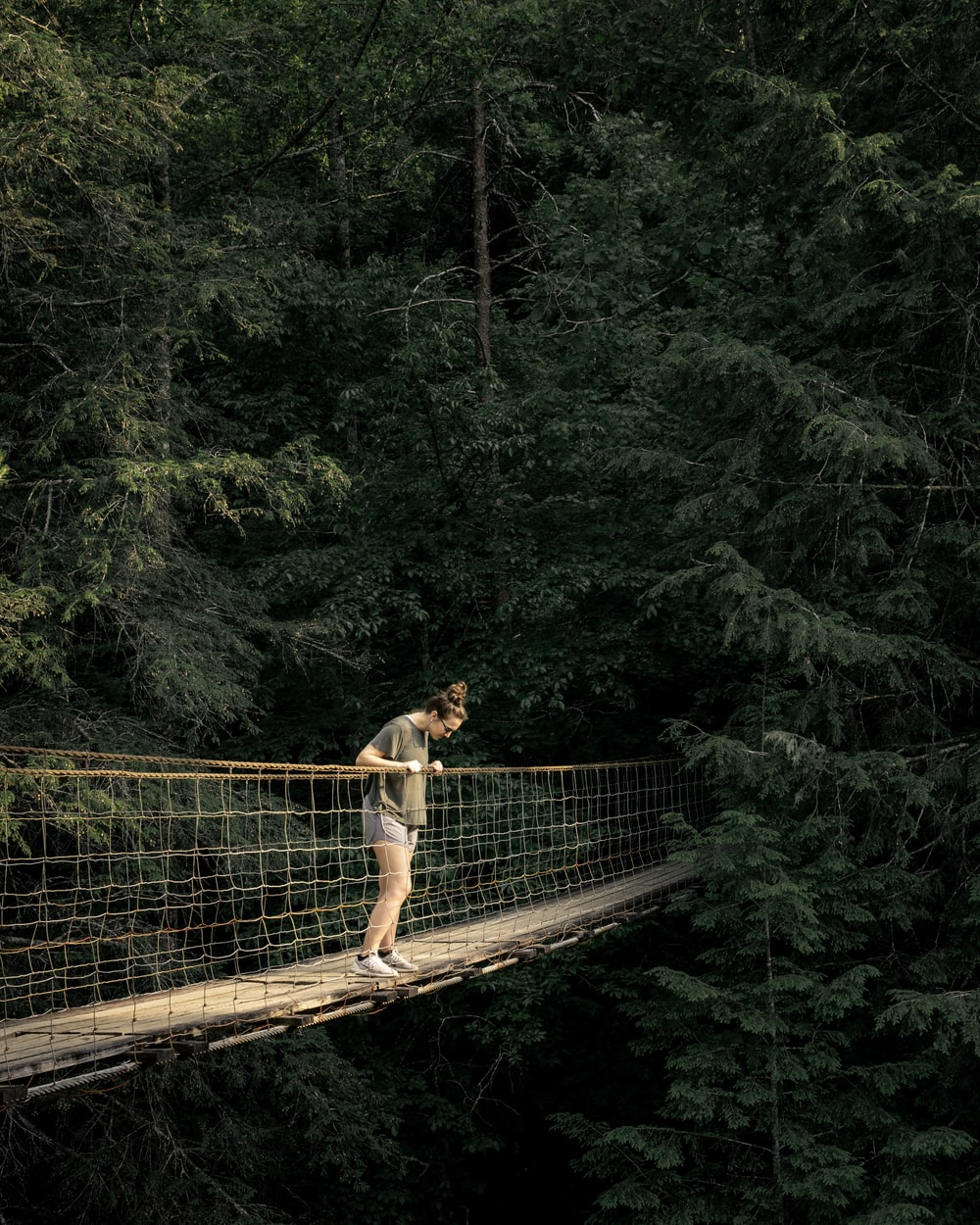 woman viewing downward on hanging bridge